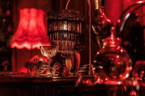 Der Ausstellungsraum ist in rotes Licht gehüllt. Es sind eine Lampe und verschiedene Gläser aus den 60er Jahren zu sehen.