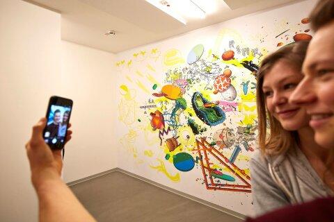 Zwei Personen machen ein Selfie vor einer Wand mit bunten Illustrationen.
