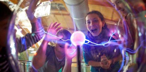Schüler stehen hinter einer violett leuchtenden Plasmakugel