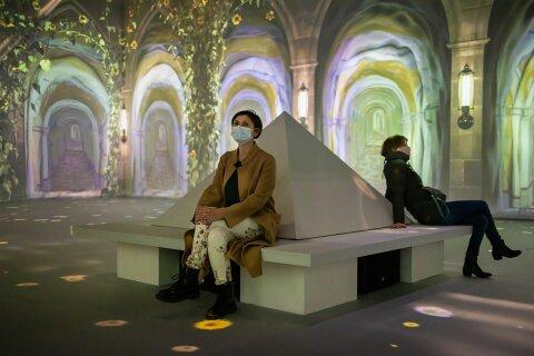 Zwei Personen sitzen in einem Ausstellungsraum und schauen sich die Kunsterwerke an, die vergrößert auf die Wände projiziert wurden.