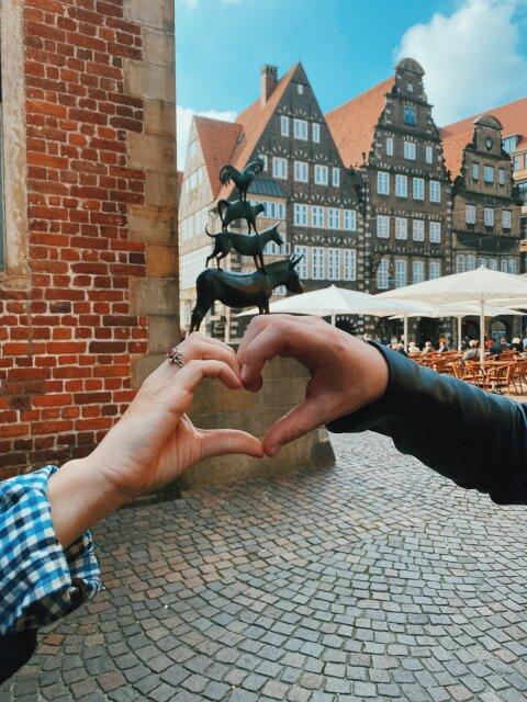 Zwei einander haltende Hände im Vordergrund, im Hintergrund die Stadtmusikanten