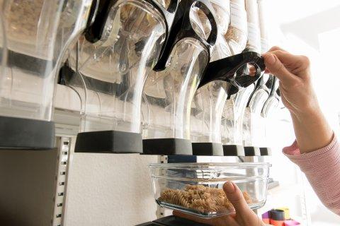 Eine Frau hält einen Glasbehälter unter eine Abfüllstation und füllt ihn mit Nudeln.