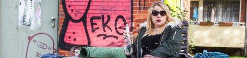 Frau sitzt mit leerer Sektflasche umgeben von Sperrmüll auf einem Gartenstuhl