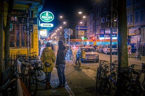 Zwei Personen stehen im Abendlicht vor der Kneipe Eisen im Viertel