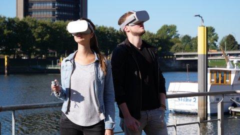 Zu sehen sind zwei Personen, die eine große Brille tragen. Sie stehen an einem Geländer, hinter dem Wasser zu sehen ist. Rechts im Bild ist ein Teil eines Schiffes zu erkennen; im Hintergrund stehen Bäume und ein braunes Gebäude.
