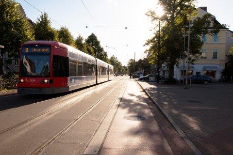 Blick in die Wachmannstraße. Eine Straßenbahn fährt vorbei. Im Hintergrund sind Autos und Personen, die die Fahrbahn überqueren. Außerdem ist eine Person auf einem Dreirad zu sehen.