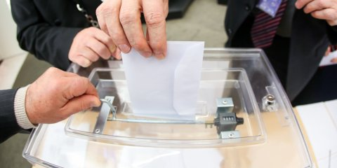 Ein Brief wird in eine Wahlurne geworfen
