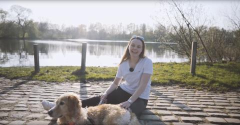 Eine junge Frau sitzt mit ihrem Hund vor einem See.