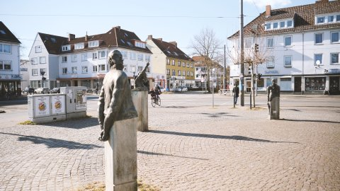 Zu sehen sind eine Kreuzung und ein Platz in Walle, auf dem Steinfiguren stehen. Die Figuren zeigen Menschen ab dem Oberkörper in verschiedenen Posen.