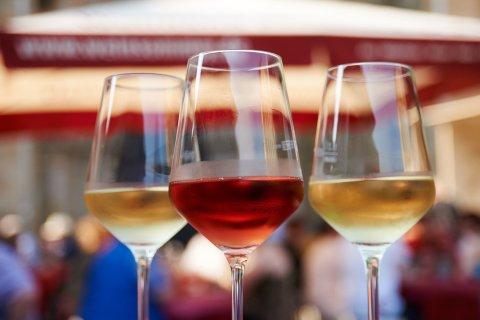 Zwei Weingläser mit einem roten und einem weißen Wein gefüllt stehen in einer Nahaufnahme vor dem Festgetümmel im Hintergrund auf einem Tisch.