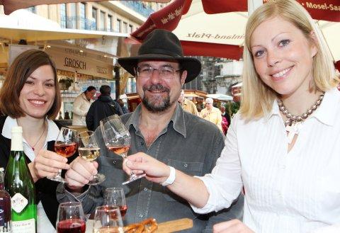 Eine Gruppe Menschen genießen Wein auf dem WeinSommer-Fest