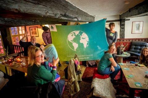 Von mehreren Personen wird eine Flagge mit einer Weltkugel hochgehalten.