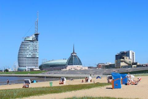 Strandkörbe am Sandstrand des Weser Strandbads. Im Hintergrund ist das Mediteraneo, das Klimahaus und das Sail City Hotel zu sehen.