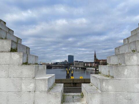 Blick auf die Weser - Links und rechts befinden sich weiße Backsteine, die wie Treppenstufen angeordnet sind.