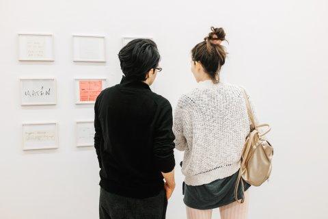 Zwei Menschen stehen mit dem Rücken zur Kamera und schauen sich Bilder an der Wand an.