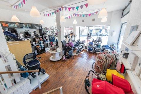 Zu sehen ist das Innere eines Ladens, in dem verschiedene Baby Artikel wie Kinderwagen, Maxi Cosi und Wickeltaschen stehen.