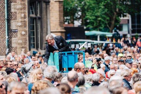 Dirigent Marko Letonja steht mitten in einer Menschenmenge auf einer Hebebühne und interagiert lachend mit dem Publikum.
