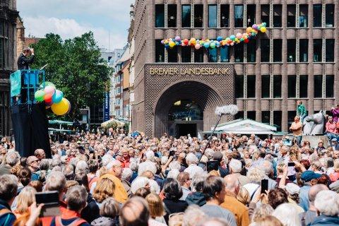 Eine Menschenmenge steht vor der Bremer Landesbank, die mit Ballons geschmückt ist. Auf einer Hebebühne in der Menge dirigiert Marko Letonja.