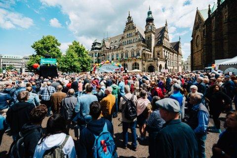 Eine Menschenmenge steht auf dem Domshof, auf einer Hebebühne in der Menge dirigiert Marko Letonja.