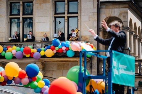 Marko Letonja ist im Vordergrund unscharf zu erkennen, im Hintergrund stehen die Bremer Philharmoniker musizierend auf einem Balkon, der mit bunten Ballons geschmückt ist.
