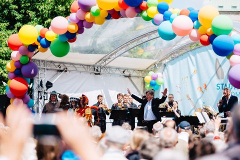 Marko Letonja steht mit ausgebreiteten Armen auf einer mit Ballons geschmückten Bühne mit den Bremer Philharmonikern. Vor der Bühne steht Publikum.