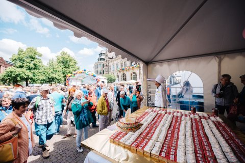 Eine Menschenmenge steht vor einem Zelt in dem Kuchen ausgeteilt wird.