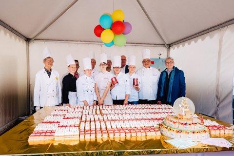 Gruppenfoto der Konditoreninnung. Vor ihnen auf einem gold geschmückten Tisch ist eine große Torte und viele kleine Tortenstücke aufgestellt.