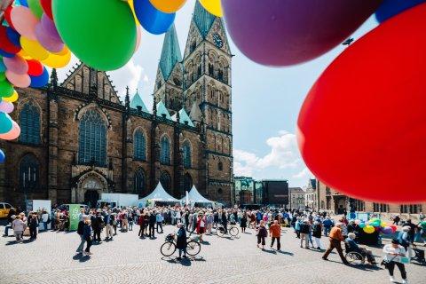Der Domshof mit Besucher*innen des Fensterkonzerts mit dem Bremer Dom. Das Bild ist eingerahmt mit bunten Luftballons.