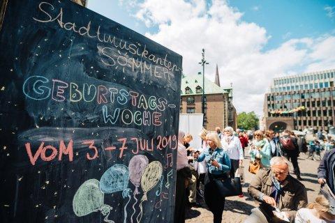 """Tafel, auf der mit bunter Kreide """"Stadtmusikantensommer Geburtstagswoche vom 3. bis 7. Juli 2019"""" steht, mit Besucher*innen des Fensterkonzerts"""