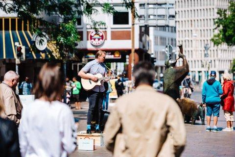 Straßenmusiker mit Gitarre steht auf der Räuberbühne in der Sögestraße.