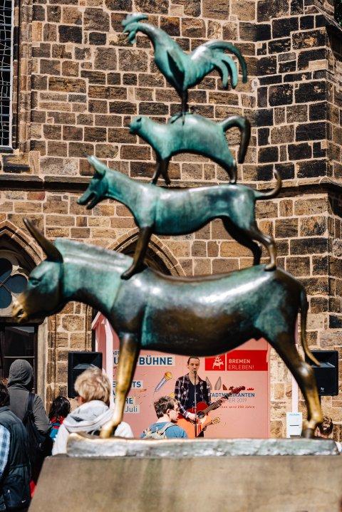 Foto von der Statue der Bremer Stadtmusikanten, im Hintergrund spielt ein Musiker Gitarre auf der Hund-Bühne