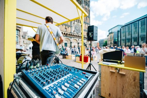 Im Hintergrund ist der Bremer Dom zu sehen, im Vordergrund ein Mischpult und ein Musiker, der Gitarre auf der Katzen-Bühne spielt.