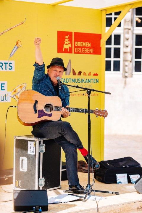 Musiker spielt Gitarre auf der gelben Katzen-Bühne und recht die Faust in die Luft