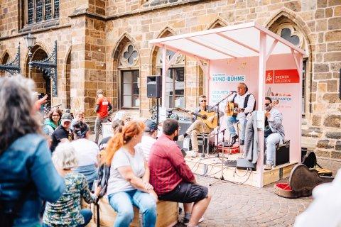 Rosafarbene Hund-Bühne mit zwei Gitarristen und Publikum.
