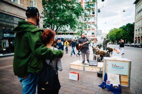 Musiker spielt auf der Räuberbühne in der Sögestraße, ein Päärchen schaut zu.