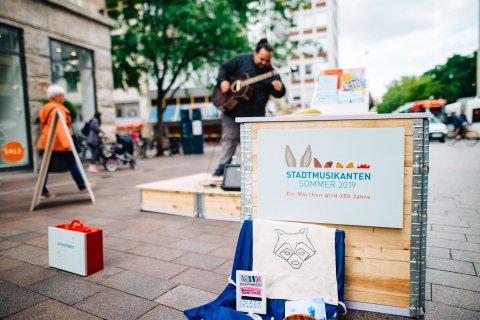 Straßenmusiker auf einer kleinen Bühne in der Sögestraße, im Vordergrund steht eine Holzbox mit dem Logo des Stadtmusikantensommers.