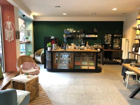 Die Glücksküche von innen. In einem gläsernen Tresen stehen verschiedene Kaffeeprodukte. Im Hintergrund stehen vor einer grünen Wand verschiedene Geräte für die Zubereitung von Kaffee und Paninis. Es stehen verschiedene Holzmöbel im Raum.
