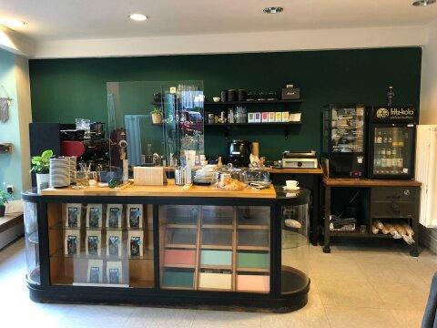 Die Glücksküche von innen. In einem gläsernen Tresen stehen verschiedene Kaffeeprodukte. Im Hintergrund stehen vor einer grünen Wand verschiedene Geräte für die Zubereitung von Kaffee und Paninis.