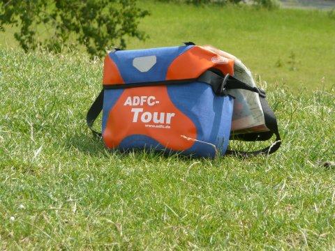 eine Umhängetasche vom ADFC steht auf einer Wiese.