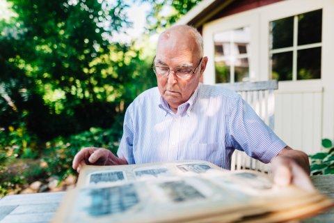 Dr. Diethelm Knauf mit einem dicken Buch im Garten