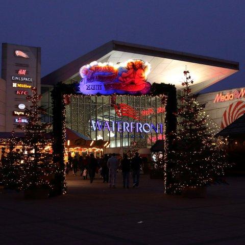Die weihnachtlich beleuchtete und geschmückte Fassade der Waterfront im Dunkeln.