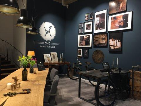 Ein Blick auf die Ladenecke von Wood.You.Love an der Bischhofsnadel. Ein großer Echtholztisch steht modern arrangiert vor einer petrolfarbenen Wand.