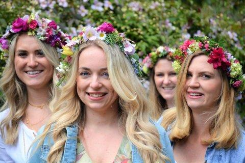 Vier Frauen mit einem Blumenkranz auf dem Kopf lachen in die Kamera.