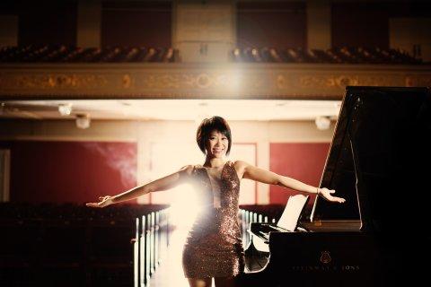 Die Pianistin Yuja Wang steht in einem leeren Konzertraum vor einem Piano. Sie trägt ein glitzerndes Kleid und breitet die Arme aus.
