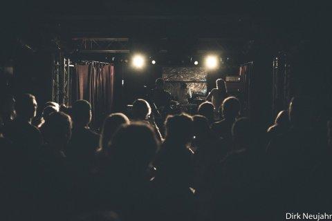 Die Bühne der Zollkantine ist in dunkles Licht gehüllt. Auf der Bühne stehen die drei Musiker der Band Rote Planeten.