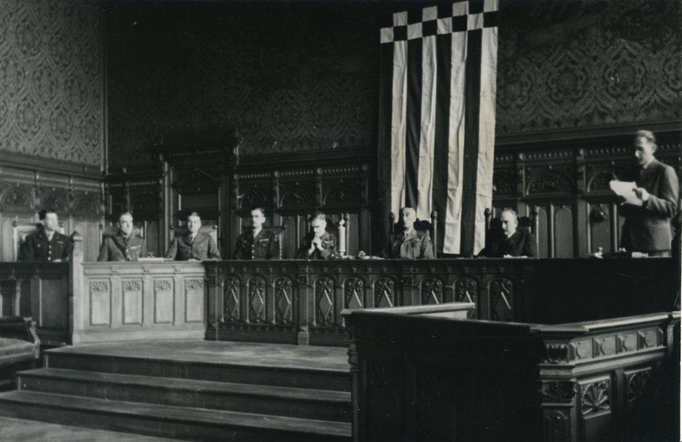 Mehrere Männer sitzen in einem großen Saal, im Hintergrund die Flagge Bremens, Schwarz-Weiß-Fotografie; Quelle: Staatsarchiv Bremen/Karl Edmund Schmidt