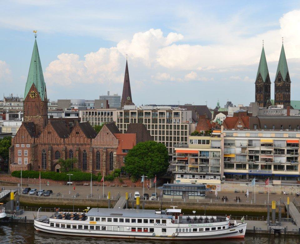 Ein Blick von einem hohen Gebäude in Richtung Bremer Innenstadt. Zu sehen sind die Schiffe an der Weser, die Martinikirche und im Hintergrund die Domspitzen