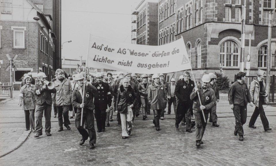 Viele Männer halten ein Banner in die Höhe, auf dem sie gegen die Schließung der AG Weser protestieren, Schwarz-Weiß-Fotografie; Quelle: Staatsarchiv Bremen