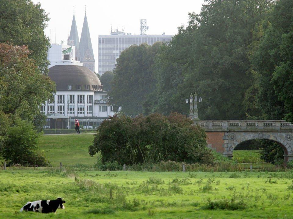 Blick eine Wiese hinunter auf eine Brücke, einen Kuppelbau, zwei Kirchtürme und andere Gebäude