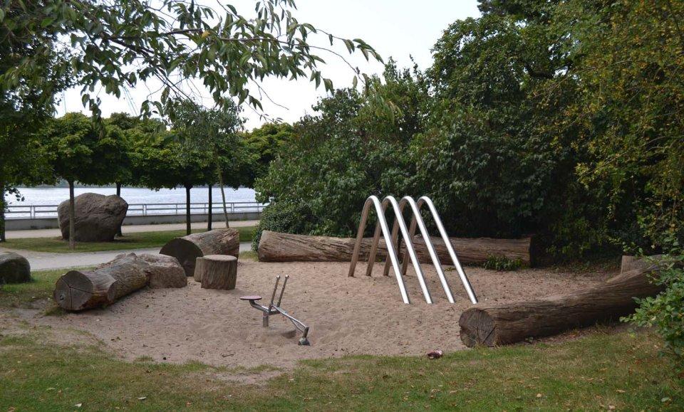 Ein kleiner Spielplatz umgeben von Bäumen, im Hintergrund ein Fluss.